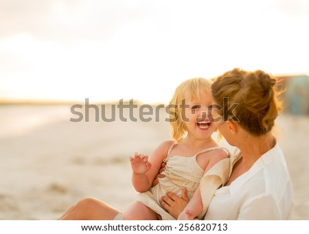 Laughing mother and baby girl sitting on beach at the evening - stock photo