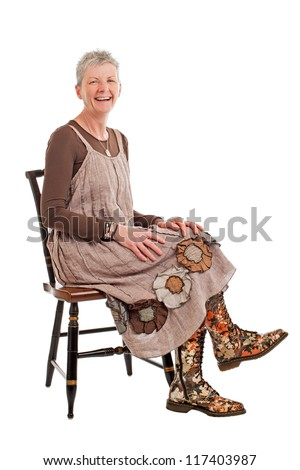 Laughing older woman with short gray hair sits sideways on chair. She wears flowered boots and brown cotton shift dress. Isolated on white background, vertical, copy space. - stock photo