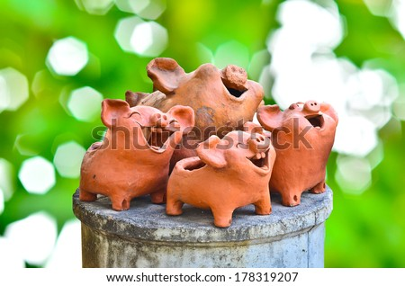 Laughing pig statue on nature background - stock photo