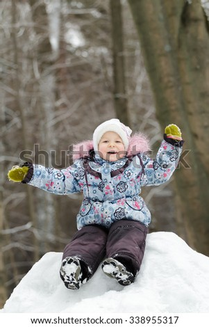 Laughing preschooler girl wearing warm clothing is having fun on snowy hill in winter forest  - stock photo
