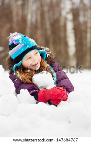 Laughing rosy girl in jacket, knitted hat and mittens lies on snowdrift - stock photo