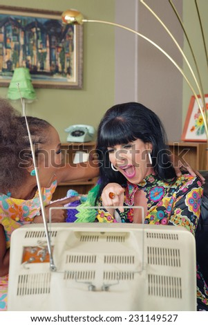 Laughing 1960s women pointing and laughing at television - stock photo