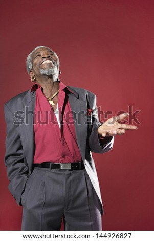 Laughing senior man in suit making hand gesture against red background - stock photo