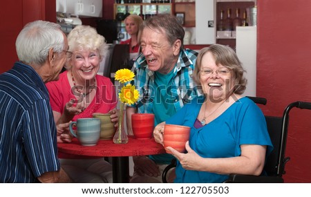 Laughing senior woman in wheelchair with friends in bistro - stock photo