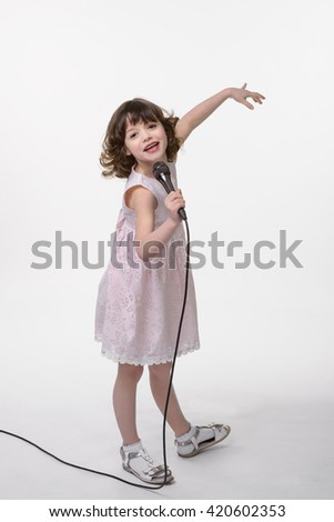 Laughing singer with black microphone in her hand, the other one is rised. Lovely curled brunette hair and cute pastel pink dress are very cool for girlish style. Positive emotions of a child. - stock photo