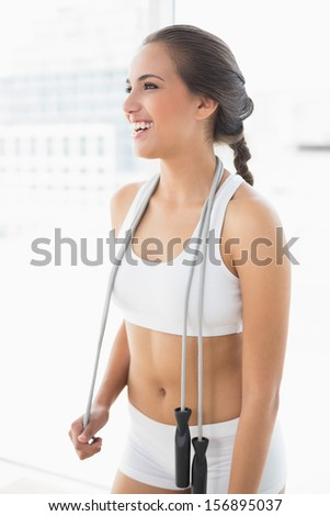Laughing sporty brunette wearing a skipping rope around the neck in bright room - stock photo