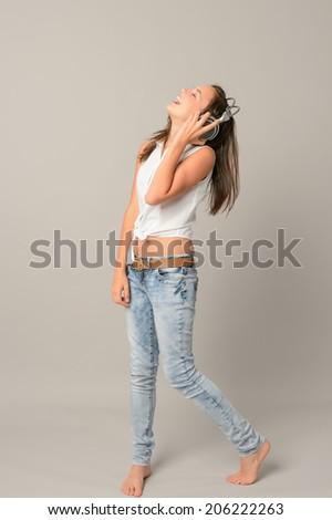 Laughing teenage girl singing enjoying music from headphones full length on gray - stock photo
