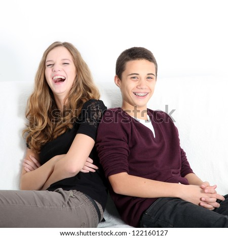 Laughing teenaged brother and sister sitting leaning on each other enjoying a good joke, square format with copyspace - stock photo