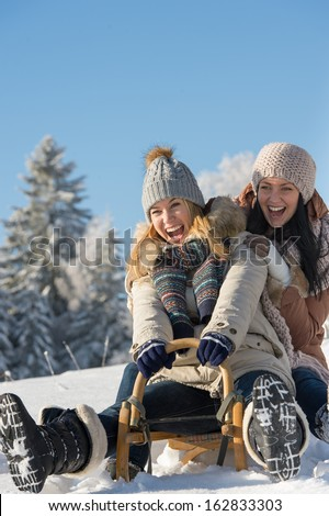 Laughing teenagers sledge downhill in wintertime enjoy snow - stock photo