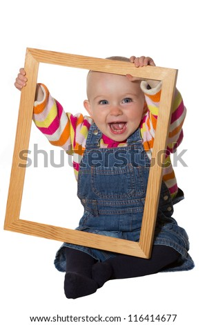 Laughing vivacious little baby girl playing with an empty wooden picture frame looking through it at the camera - stock photo