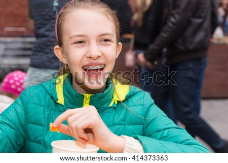 Laughing vivacious pretty young girl with orthodontic braces on her teeth sitting outdoors eating at a table - stock photo
