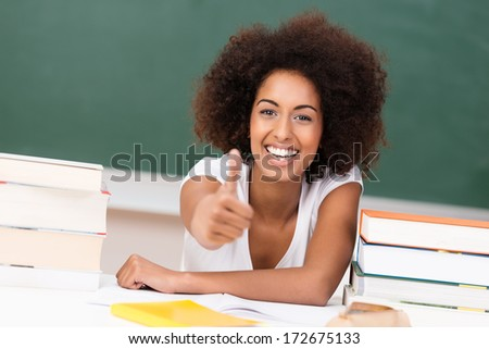 Laughing vivacious young African American woman student giving a thumbs up of approval and success as she sits at her desk with her text books - stock photo