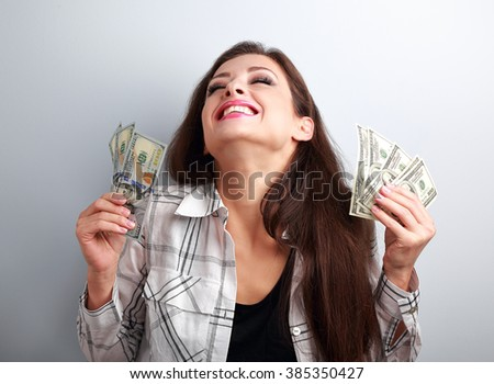 Laughing winner young woman holding dollars with closed eyes on blue background - stock photo