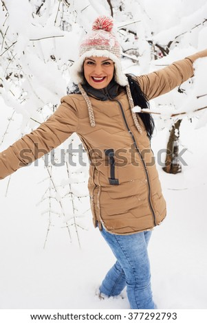 Laughing woman having fun in park with snow - stock photo
