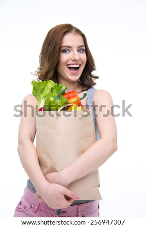 Laughing woman holding a shopping bag full of groceries - stock photo
