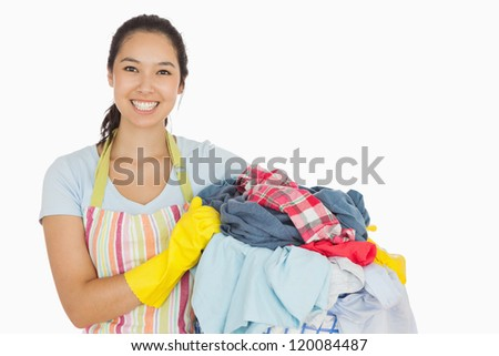 Laughing woman holding laundry basket wearing apron and rubber gloves - stock photo
