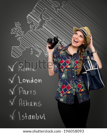 Laughing woman holding  photo camera in background draw list of visited cities  - stock photo