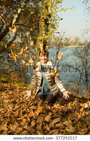 Laughing woman in park tossing autumn leaves - stock photo