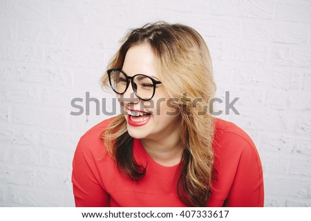Laughing woman in red dress and glasses on white brick wall background - stock photo