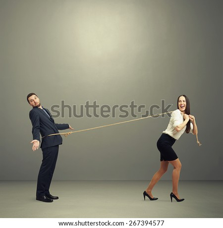 laughing woman lugging man in perplexity. photo on dark background - stock photo