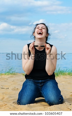 Laughing woman on the beach - stock photo