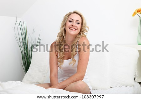 Laughing woman relaxing on her bed Laughing woman with a lovely smile relaxing on her bed in her lingerie as she enjoys a leisurely morning - stock photo