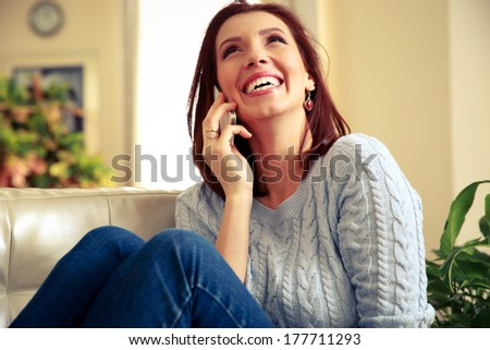 Laughing woman talking on the phone and looking up at home - stock photo