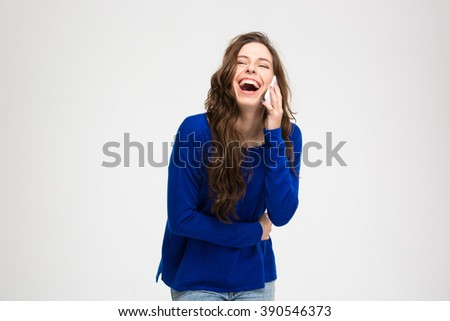 Laughing woman talking on the phone isolated on a white background - stock photo