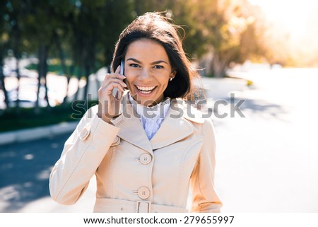 Laughing woman talking on the phone outdoors and looking at camera - stock photo