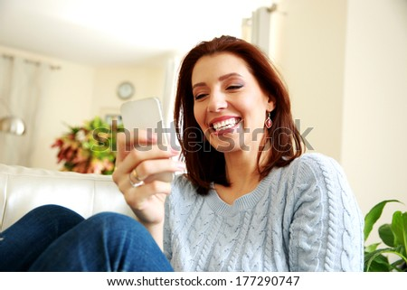 laughing woman using smartphone at home - stock photo