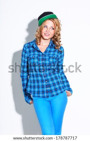 laughing woman wearing cap posing near white wall - stock photo