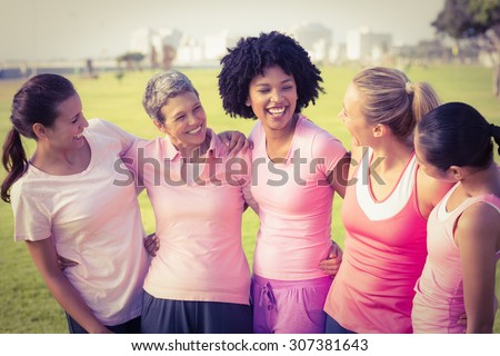 Laughing women wearing pink for breast cancer in parkland - stock photo