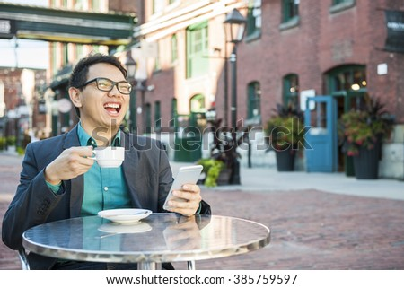 Laughing young asian man sitting in outdoor cafe with mobile phone holding cup of coffee enjoying success - stock photo