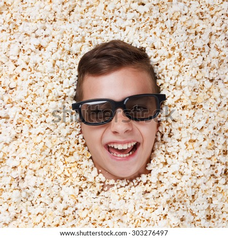 Laughing young boy in stereo glasses watching a movie from popcorn - stock photo