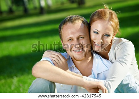 Laughing young couple embraces in a summer garden - stock photo