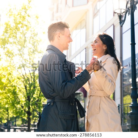 Laughing young couple flirting outdoors - stock photo