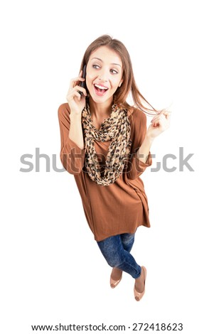 Laughing young fashion beauty talking on the mobile phone. High angle view wide lens full body length portrait isolated over white background - stock photo