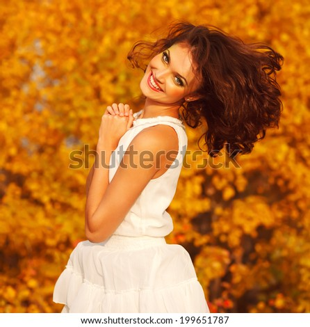 Laughing young girl in a white dress in the autumn park - stock photo