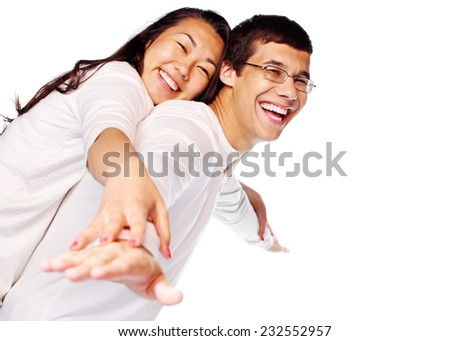 Laughing young interracial couple in love having fun posing as flying on isolated white background - stock photo