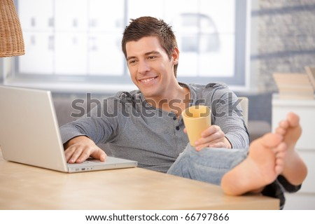 Laughing young man enjoying using laptop computer at home, holding tea cup, looking at screen with bare feet on table.? - stock photo