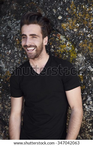 Laughing young man in t-shirt against rock - stock photo