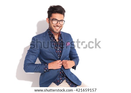 laughing young man unbuttoning his coat while seated in studio - stock photo