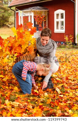 Laughing young mother and her cute little daughter playing in colorful yellow and orange autumn leaves while collecting a basket full of leafy twigs to decorate the house - stock photo