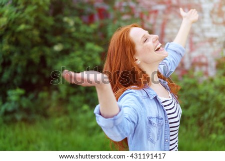 Laughing young redhead woman rejoicing in spring standing with closed eyes and her arms outspread in a lush green spring garden - stock photo
