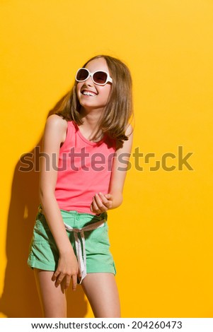 Laughing young summer girl looking away. Three quarter length studio shot on yellow background. - stock photo