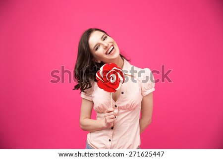 Laughing young woman holding lollipop over pink background and looking at camera - stock photo