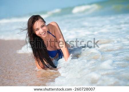 Laughing young woman posing on the beach - stock photo