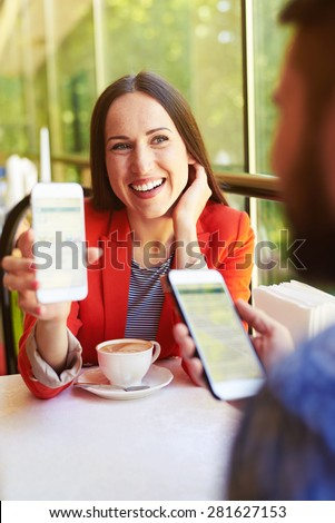 laughing young woman showing her mobilephone to man at cafe - stock photo