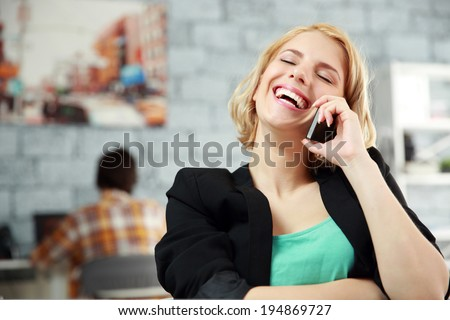 Laughing young woman talking on the office in office - stock photo