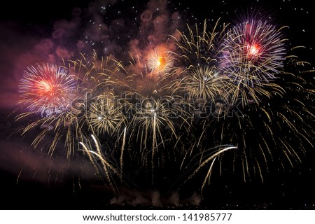 Launching of Colorful fireworks of various colors over night sky - stock photo